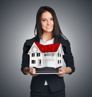 Business woman showing house symbolizing sale of real estate