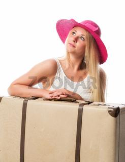 mädchen sitzt vor einem koffer und wartet