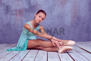 young ballerina sitting on wooden floor
