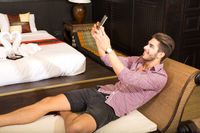 Young man in a hotel room taking a selfie