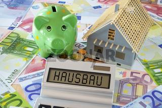 Das Wort Hausbau auf Display von Taschenrechner und Sparschwein