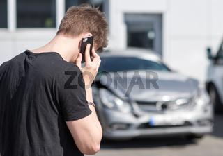 junger mann telefoniert nach einem autounfall