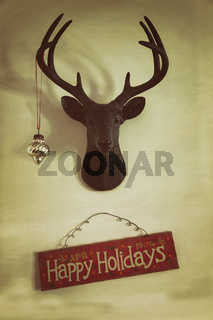 Closeup of mounted deer head with christmas ornament and holiday sign