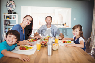 Portrait of smiling family with food on dining table