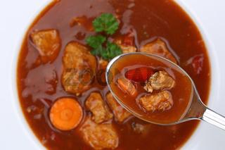 Gulasch Suppe Gulaschsuppe essen Suppentasse mit Fleisch und Paprika auf Löffel