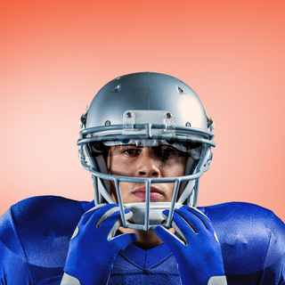 Composite image of portrait of serious sportsman holding helmet