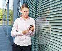 Business Frau schaut auf Smartphone