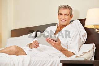 Mann benutzt Tablet im Hotelzimmer