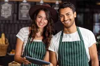 Smiling baristas using tablet