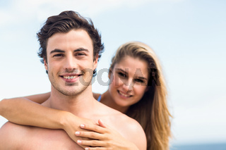 Happy couple in swimsuit looking at camera and embracing