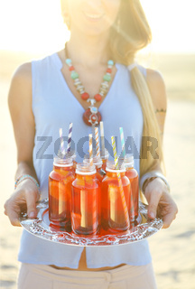 Happy young woman holding a dish with a drinks at sunset party