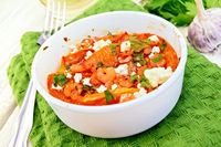 Shrimp and tomatoes with feta in white bowl on light board