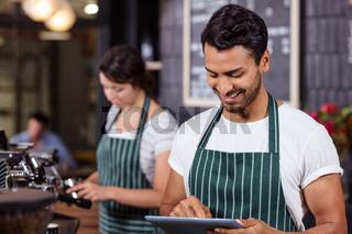 Smiling barista using tablet