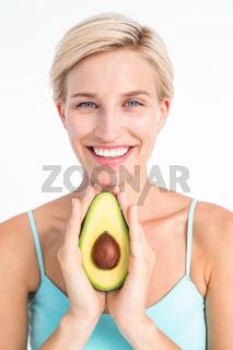 Attractive woman showing half of an avocado