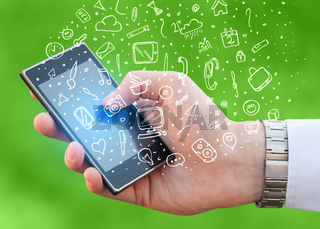 Hand holding smartphone with hand drawn media icons and symbols