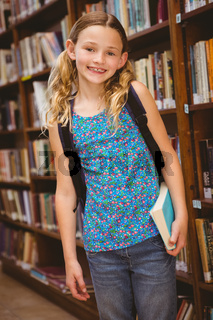 Cute little girl holding book in library