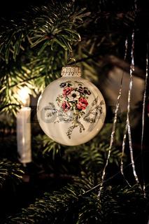 Weiße Christbaumkugel mit Blumenmuster und Glitzer am Weihnachtsbaum