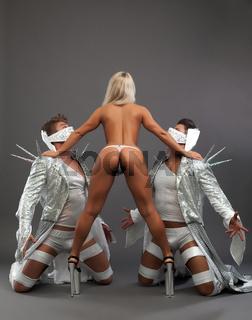 BDSM dance. Nude dominatrix manages her slaves