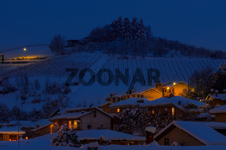Houses and snowy hill in evening.