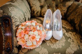 bridal bouquet and the bride shoes on chair