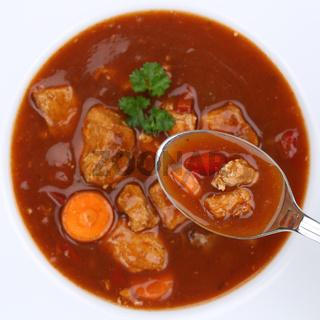 Gesunde Ernährung Gulasch Suppe Gulaschsuppe essen mit Fleisch und Paprika auf Löffel