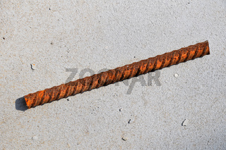 Cut piece of corroded stained rusty metal armature fitting on bubbled concrete floor