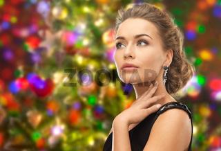 beautiful woman wearing earrings over lights