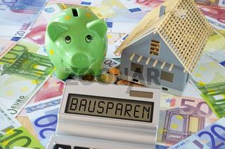 Das Wort Bausparen auf Display von Taschenrechner und Sparschwein