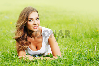 young woman in white dress lying on grass