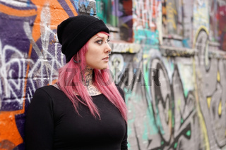 woman with pink hair piercings and tattoos leaning against graffiti wall