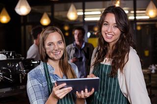 Pretty baristas using tablet