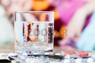 glass with water and pills on table close up
