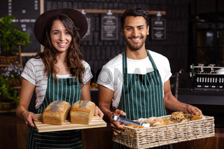 Smiling baristas holding bread and desserts