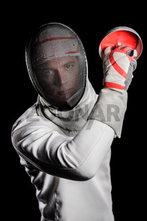 Close-up of man wearing fencing suit practicing with sword