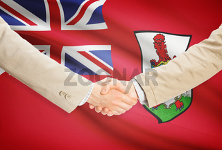Businessmen shaking hands with flag on background - Bermuda