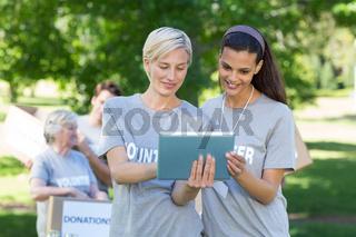 Happy volunteer friends using tablet pc