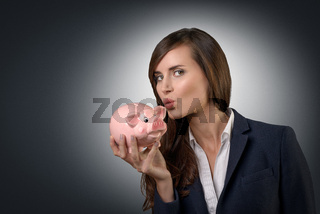 Geschäftsfrau küsst ein Sparschwein