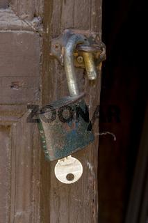 Close up of padlock hang on old wooden door