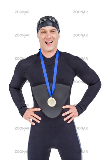 Victorious swimmer posing with gold medal around his neck