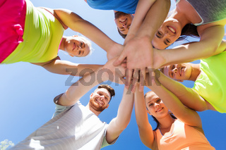 group of happy friends with hands on top outdoors
