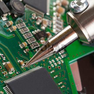 Soldering iron and microcircuit - closeup studio shot