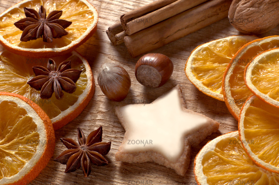 Christmas spices, cinnamon star and orange slices on wooden board