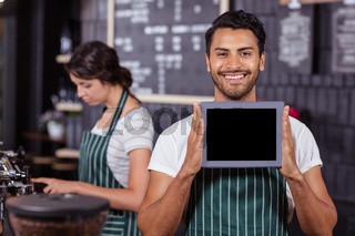 Smiling barista showing tablet at the camera