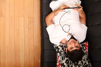 Young man with a Tablet PC and Headphones on the Sofa