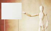 Wooden puppet points to blank white broadsheet with its hand. Conceptual image about presentation