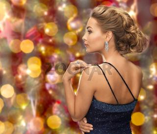 beautiful woman with diamond earring over lights