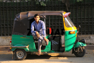 Driver sitting in his tuk-tuk in the street of Delhi, India
