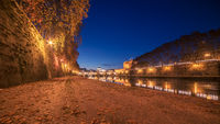 Autumn leaves on embankment of Tiber River in Rome, Italy