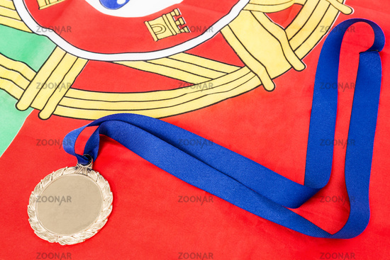 Close-up of gold medal on portugual flag