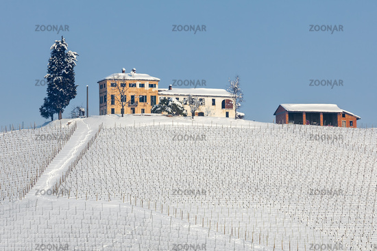 Rural houses on snowy hill in Italy.